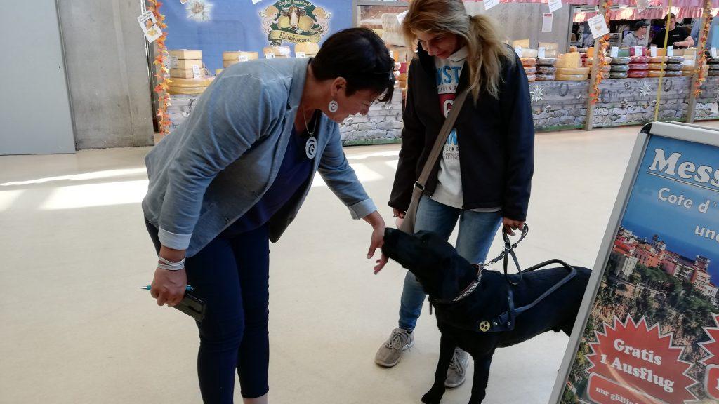 Eine Dame begrüßt ein Reha-Hund auf einer Messe