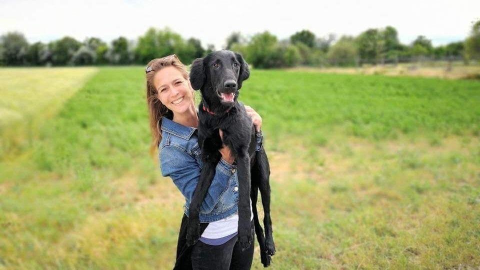 Rehahunde-Schule Besitzerin hält fröhlich eine schwarze Labrador Hundin Peppa auf den Händen